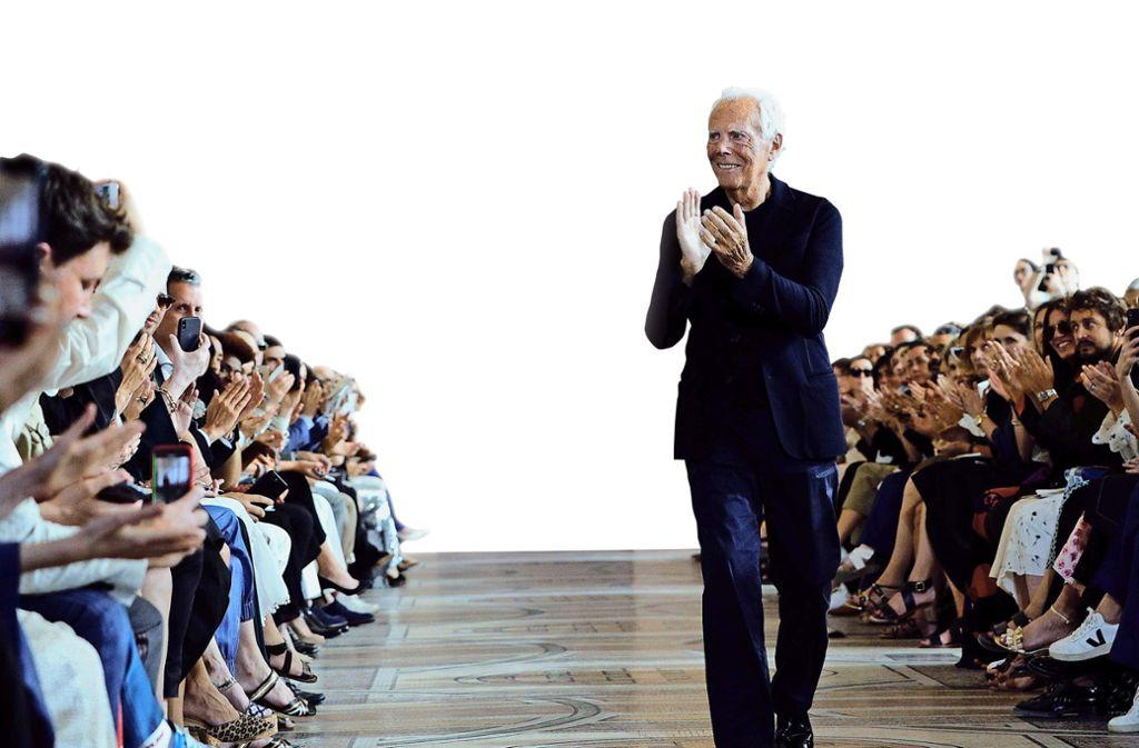 Überall auf der Welt ein gefeierter Star: der italienische Modedesigner Giorgio Armani in dem Outfit, das er zum Standard des  modebewussten Mannes gemacht hat: lässig-eleganter Anzug, einfaches T-Shirt. Foto: dpa