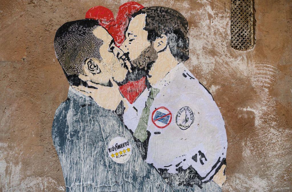 Straßenkunst an einer Hauswand in Rom: Luigi di Maio (l), Vorsitzender der Partei Fünf Sterne, und Matteo Salvini, Vorsitzender der Lega-Partei, knutschen sich an die Regierung. Mit einem hat das Liebenpaar aber nicht gerechnet: Silvio Berlusconi. Foto: AP