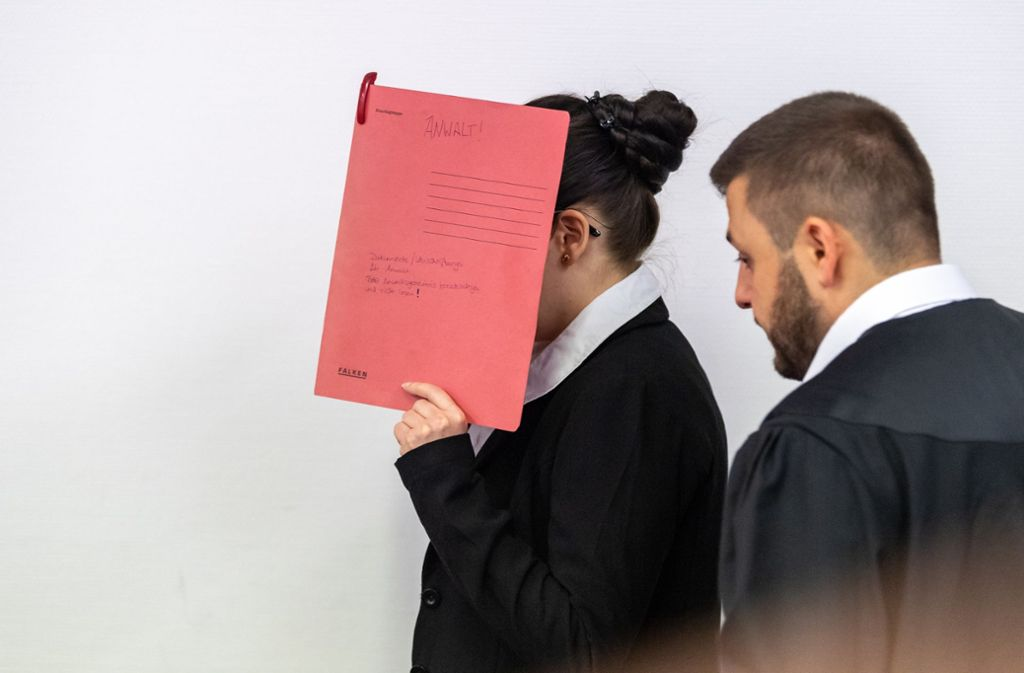 Die Angeklagte, die sich der Terrormiliz Islamischer Staat (IS) im Irak angeschlossen haben soll, hält sich beim Betreten des Gerichtssaals einen roten Aktendeckel vors Gesicht. Foto: dpa