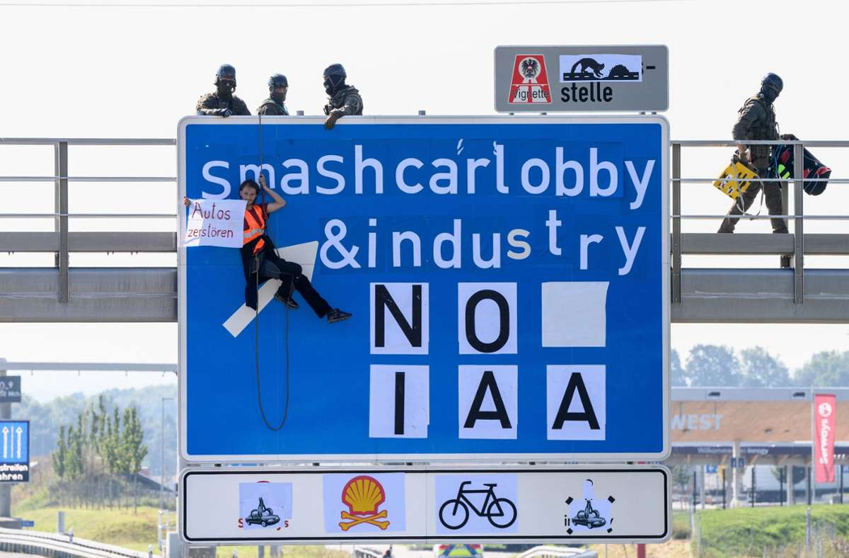 Ein Aktivist hängt bei einer Banneraktion an einer Schilderbrücke über der Autobahn A9 bei Fürholzen in Fahrtrichtung München. Foto: dpa/Matthias Balk
