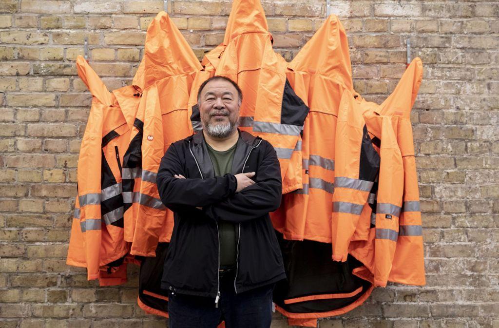 """Der chinesische Künstler Ai Weiwei steht vor seinem Kunstwerk """"Safety Jackets Zipped the Other Way"""". Foto: dpa/Christoph Soeder"""