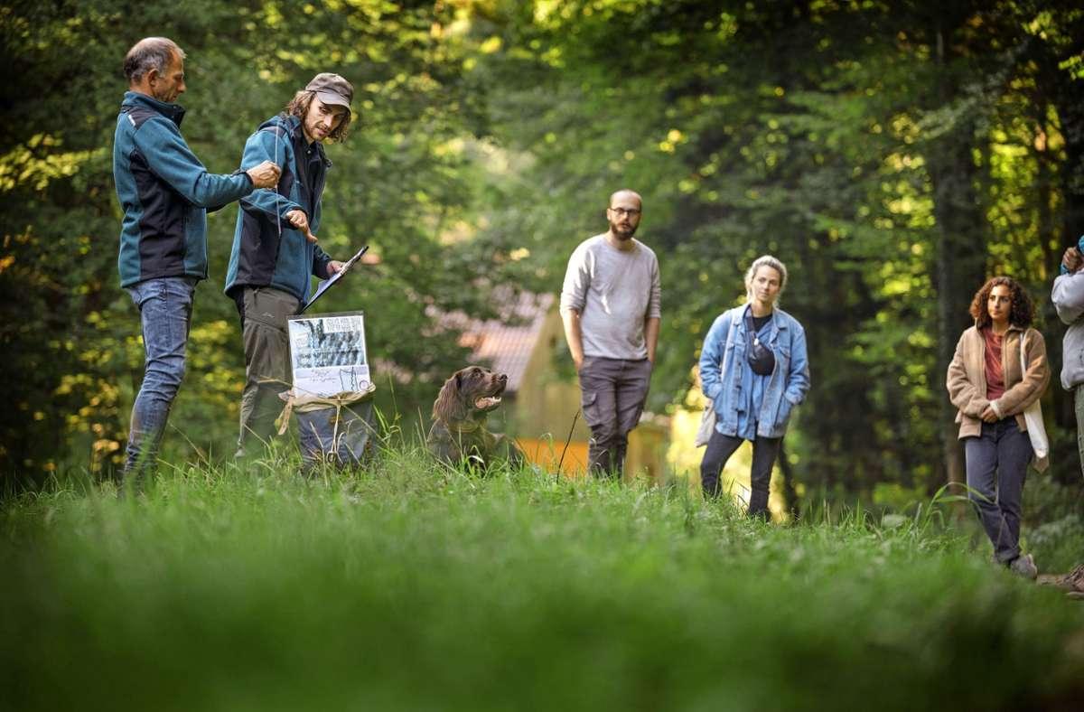 Förster Kilian Knötzele  (Zweiter von links) veranschaulicht mit Schaubildern, wie das Holz einst auf dem Flüsschen Wieslauf abtransportiert wurde. Foto: Gottfried Stoppe/l