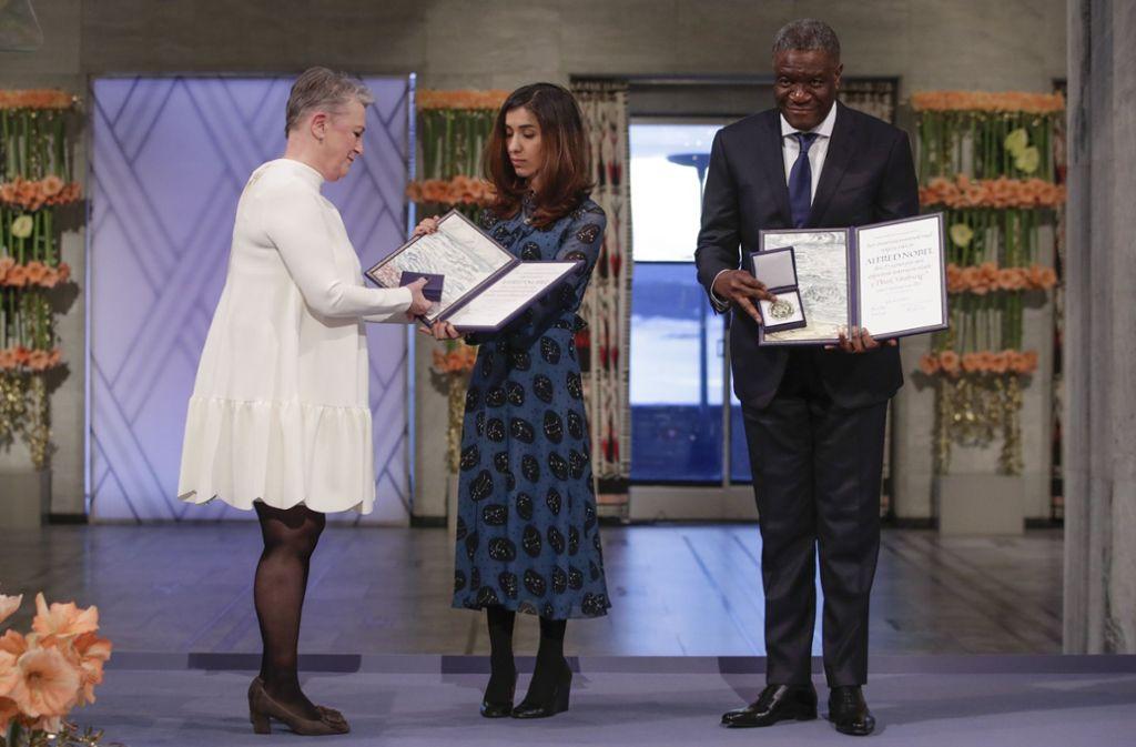 Berit Reiss-Andersen (l) überreicht den Friedensnobelpreis an Denis Mukwege (r), Arzt aus dem Kongo, und Nadia Murad, Menschenrechtsaktivistin aus dem Irak, im Rathaus von Oslo. Foto: NTB scanpix