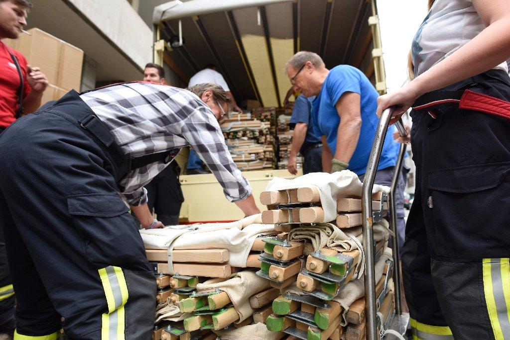 Helfer des Deutschen Roten Kreuzes laden Feldbetten für Flüchtlinge in der Stuttgarter Olgastraße aus. Foto: www.7aktuell.de | Oskar Eyb