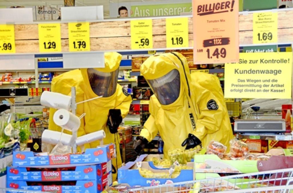 In Schutzanzüge gehüllt, durchsuchen Feuerwehrleute den ganzen Laden. Die Spinne, so es eine gibt, finden sie nicht. Fotos von der Suchaktion zeigen wir in der Bilderstrecke. Foto: Gaby Mayer