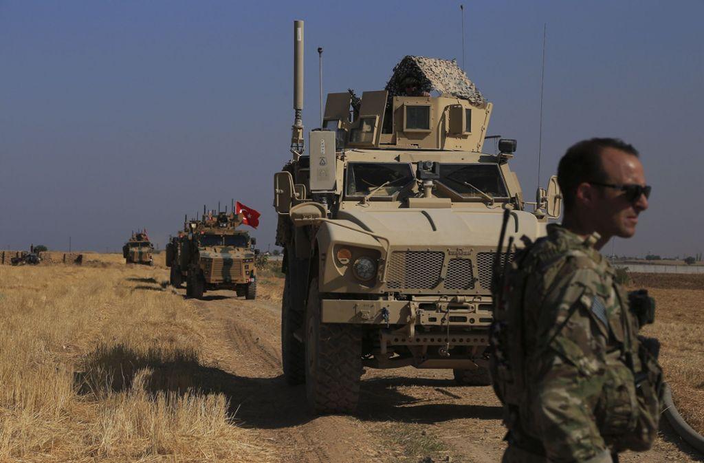 Türkische und amerikanische Panzerfahrzeuge patrouillieren bei der gemeinsamen Bodenpatrouille in der sogenannten «Sicherheitszone» auf der syrischen Seite der Grenze zur Türkei. Die US-Truppen sind nun in den Westirak verlegt worden. Foto: dpa/Baderkhan Ahmad