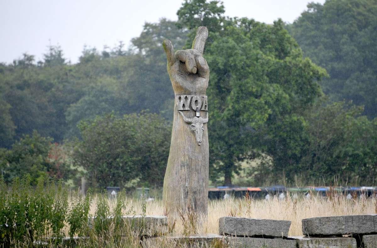 Eine Skulptur mit dem Wacken-Open-Air-Zeichen WOA und dem Metal-Gruß steht einsam auf dem Festivalgelände.Foto:dpa/Carsten Rehder Foto: