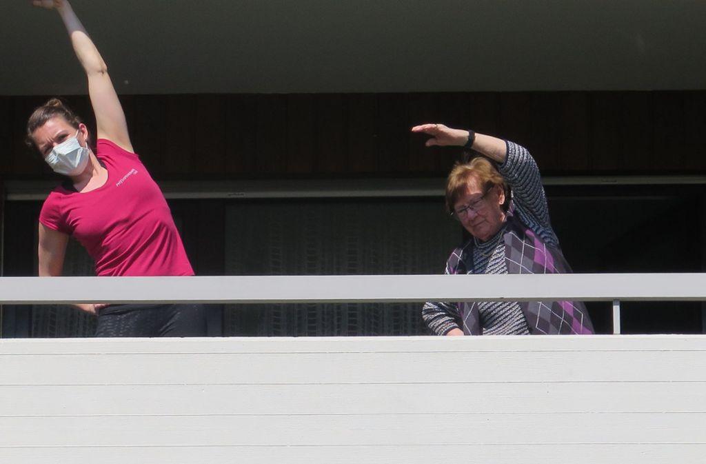Die Physiotherapeutin Sonja Friedmann und eine Patientin nutzen die Übungseinheit, um auf einem Fellbacher Balkon gleich Sonne und frische Luft zu tanken. Foto: Brigitte Hess