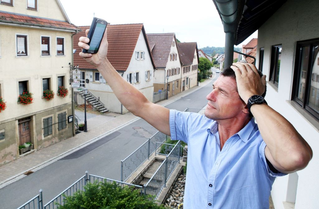 Ortsvorsteher Heiko Gieser versucht in Bittelbronn, mit seinem Handy Daten zu empfangen.  Auch das Kabelnetz ist schlecht in dem Ortsteil von Möckmühl nördlich von Heilbronn. Foto: Ralf Schäfer