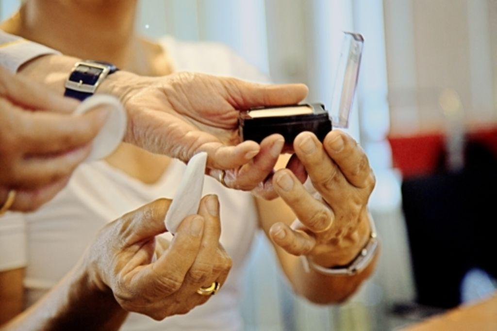Helfende Hände: die Kosmetikerin unterstützt die Frauen, schminken sollen sie sich aber selbst, um es später allein zu können. Foto: Ines Rudel