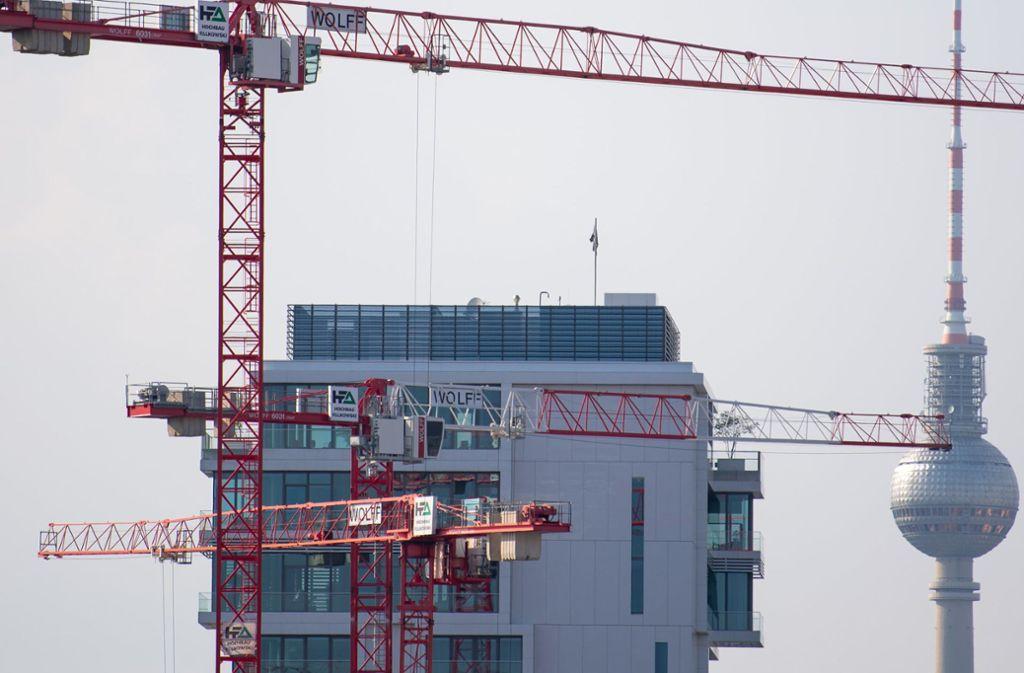 Hohe Baukräne auf einer Baustelle und im Hintergrund der Berliner Fernsehturm: Das Abgeordnetenhaus der Hauptstadt hat über den Mietendeckel abgestimmt. Foto: dpa/Monika Skolimowska