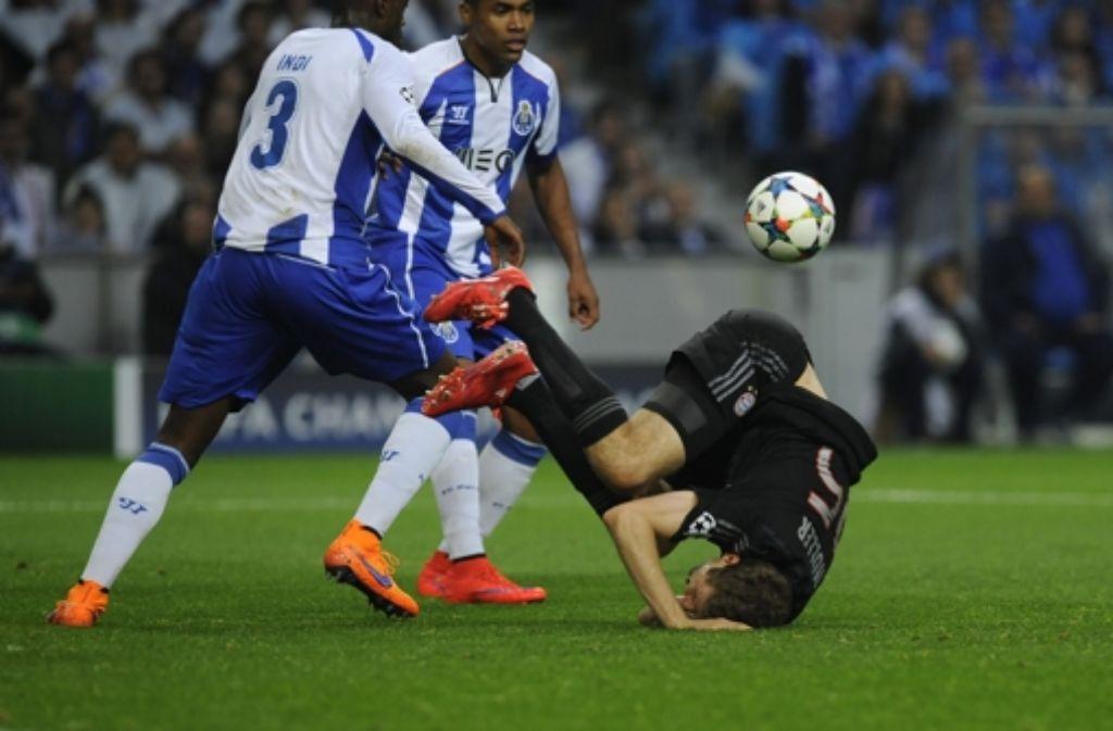 Bayern-Spieler Thomas Müller fällt vor Portos Bruno Martins Indi (links) and Alex Sandro während des Viertelfinales der Champions League. Foto: AP