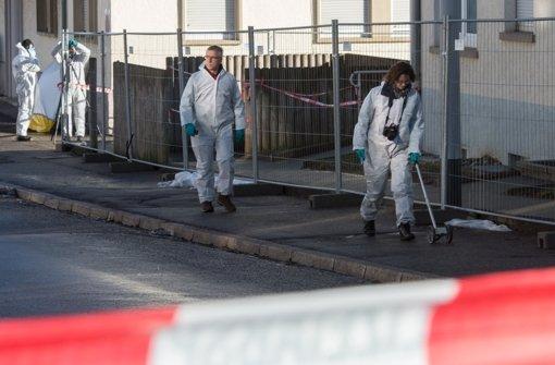 Kriminalbeamte untersuchen in Villingen-Schwenningen die Straße vor einem Flüchtlingsheim. Unbekannte haben eine Handgranate über den Zaun der Unterkunft geworfen. Foto: dpa