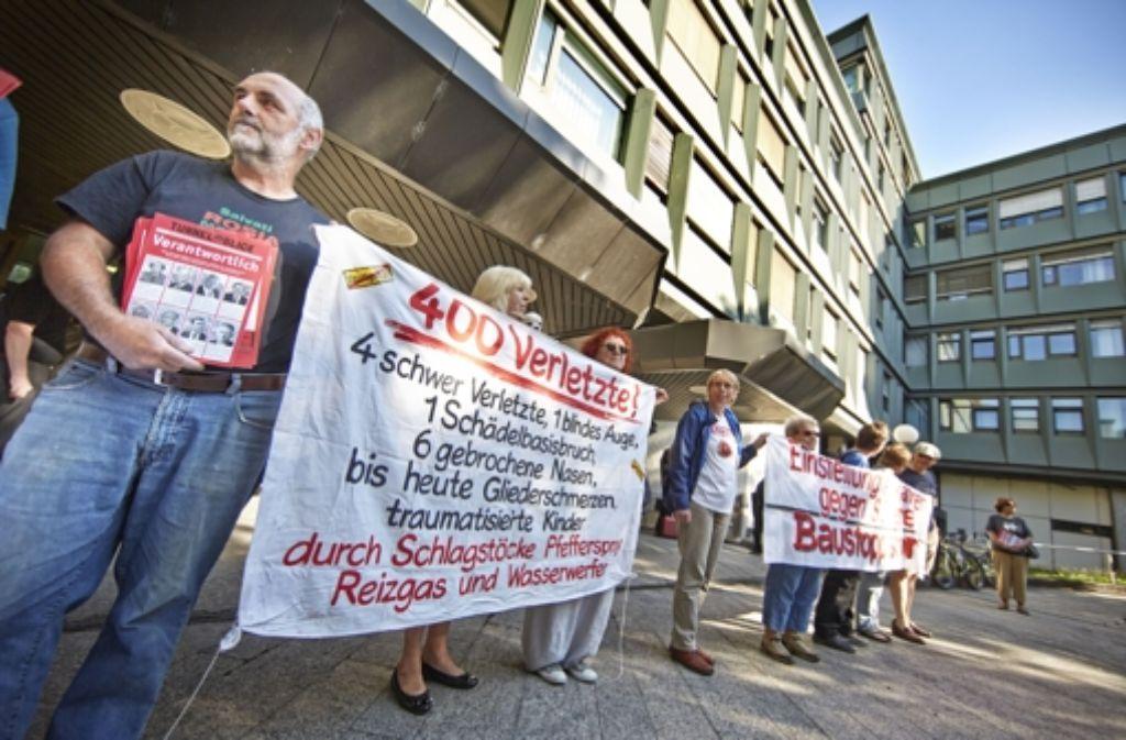 Verhaltener Protest vor Prozessbeginn: Stuttgart-21-Gegner weisen vor dem Gericht auf die Opfer des 30. September hin. Bilder vom Prozessauftakt sehen Sie in unserer Fotostrecke. Foto: dpa, Heinz Heiss