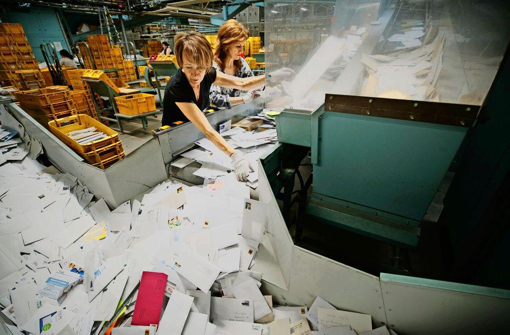 Akkordarbeit: Mit beiden Händen trennen Mitarbeiterinnen Groß- von Standardbriefen. Foto: Gottfried Stoppel