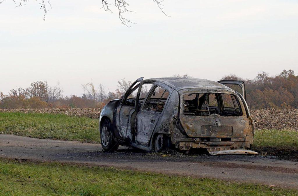 Das ausgebranntes Auto steht am Tatort. Ein 47 Jahre alter Mann soll ein Auto angezündet haben, in dem seine getrennt von ihm lebende Ehefrau saß. Foto: dpa/Andreas Rosar