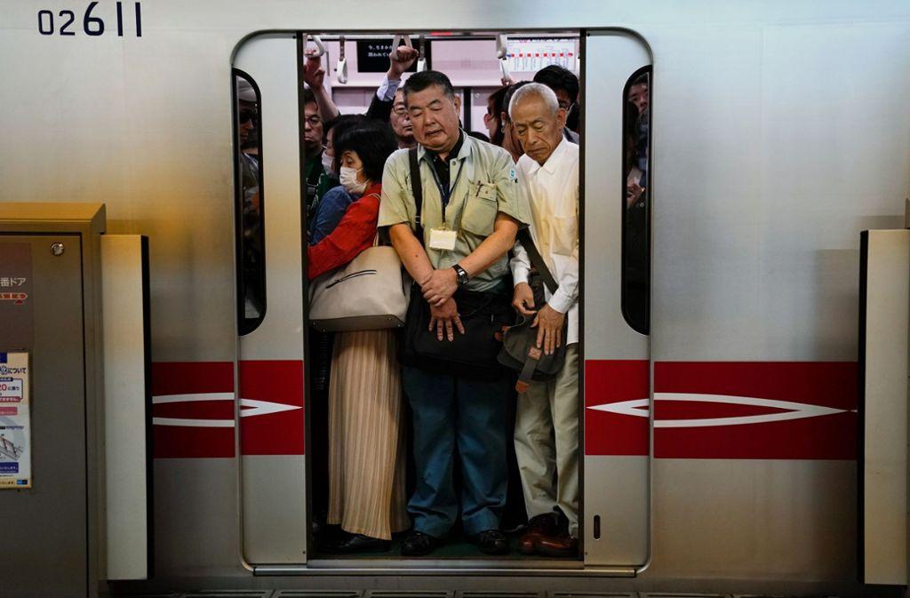Menschen stehen dicht gedrängt in einem Pendlerzug, als sich die Zugtüren am Bahnhof Shinjuku in Tokio schließen. In japanischen U-Bahnen herrscht qualvolle Enge. Foto: Jae C. Hong/AP/dpa