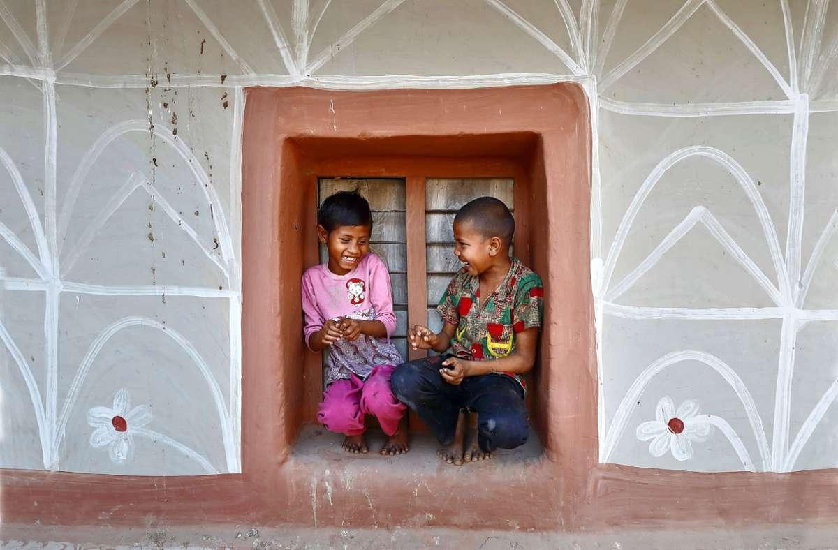 Angehörige der Volksgruppe der Santal bemalen häufig ihre Häuser mit floralen Ornamenten. Den Kindern bietet das Lehmhaus Schutz beim Spiel. Foto: Pern Images/Noor Ahmed Gelal