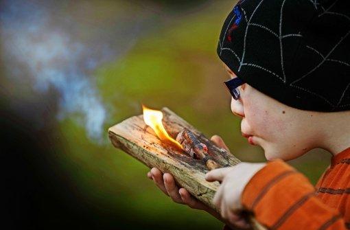Nur langsam frisst sich die Glut in das Holz – das verlangt den Schülern Geduld ab. Foto: Gottfried Stoppel