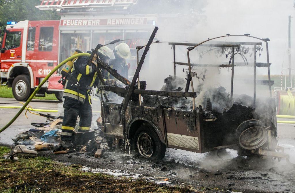 Der ausgebrannte Anhänger wird von der Feuerwehr gelöscht. Foto: SDMG
