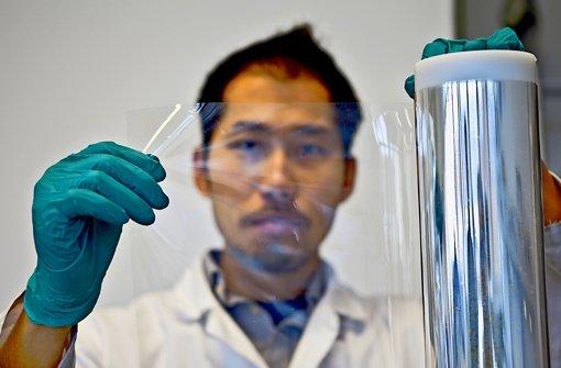 Der Stuttgarter Fraunhofer-Forscher Victor Siong zeigt eine transparente Folie, die dank Nanoröhrchen für flexible Displays genutzt werden kann. Foto: Martina Bräsel
