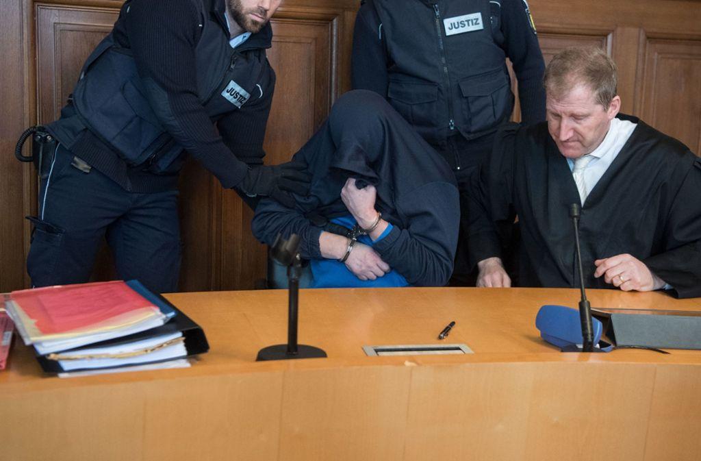Der Angeklagte zieht sich seine Jacke über sein Gesicht. Foto: dpa