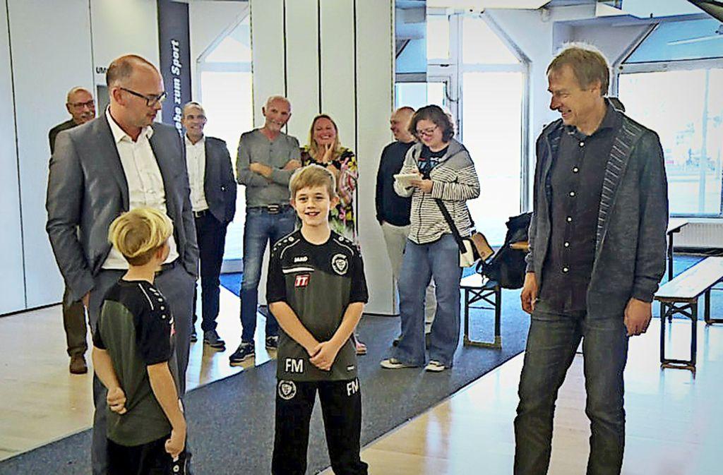 Der Oberbürgermeister Frank Dehmer (links) und der Ex-Profifußballer Jürgen Klinsmann (vorne rechts) mit zwei Kindern in den Räumlichkeiten in der Kanalstraße 19. Hier soll im Frühjahr 2019 ein Kinderzentrum der Agapedia-Stiftung entstehen. Foto: Agapedia