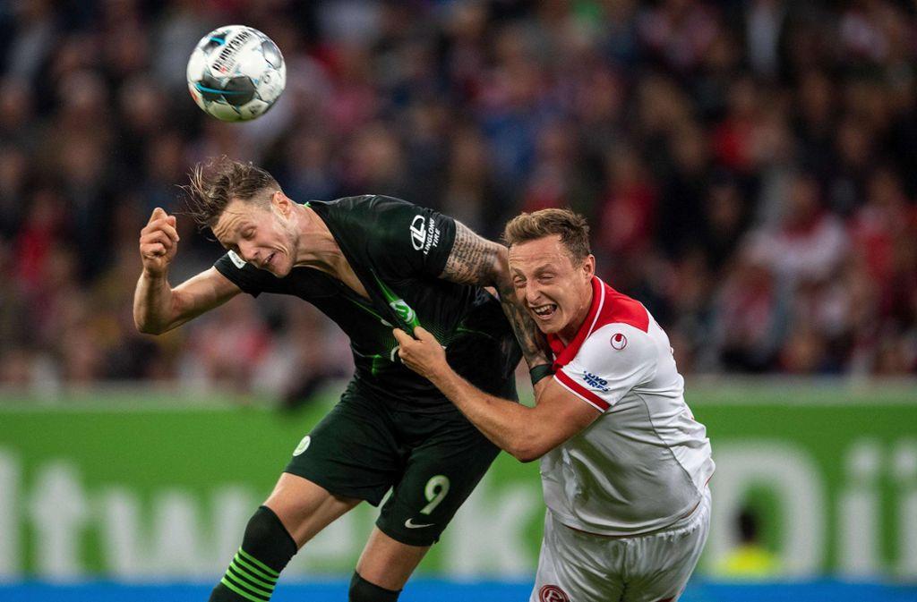 Düsseldorfs Verteidiger  Robin Bormuth verliert das Kopfball-Duell gegen Wout Weghorst. Foto: AFP/MARIUS BECKER