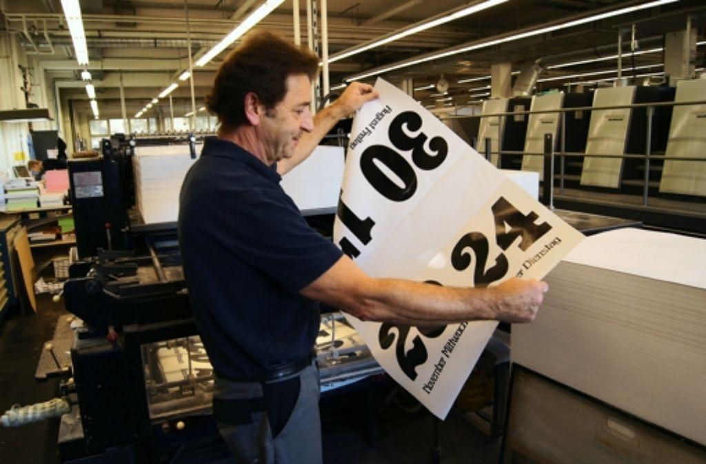 Wenn die Bögen aus der Druckmaschine kommen, prüft R. Bär, ob alles stimmt. Foto: Bürkle
