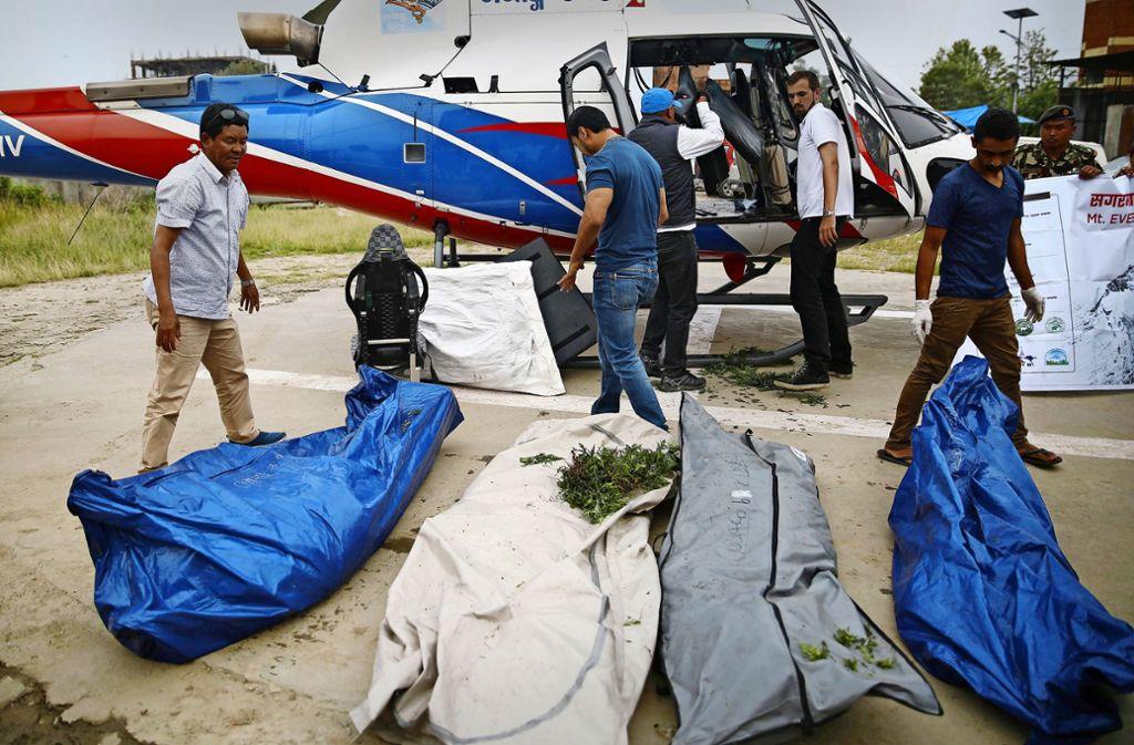 Ein Team der Nepal Army lädt die sterblichen Überreste von vier Bergsteigern aus einen Hubschrauber. Am Mount Everest sind binnen zwei Tagen vier Bergsteiger ums Leben gekommen. Foto: Skanda Gautam/ZUMA Wire/dpa