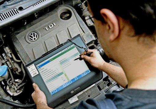 Allein in Deutschland sind nach jetzigem Kenntnisstand 2,4  Millionen VW-Fahrzeuge  von der Manipulationssoftware betroffen. Ein Kfz-Servicetechniker steht  mit einem Auslesegerät vor einem vom Abgas-Skandal betroffenen 2.0l TDI Dieselmotor. Foto: dpa