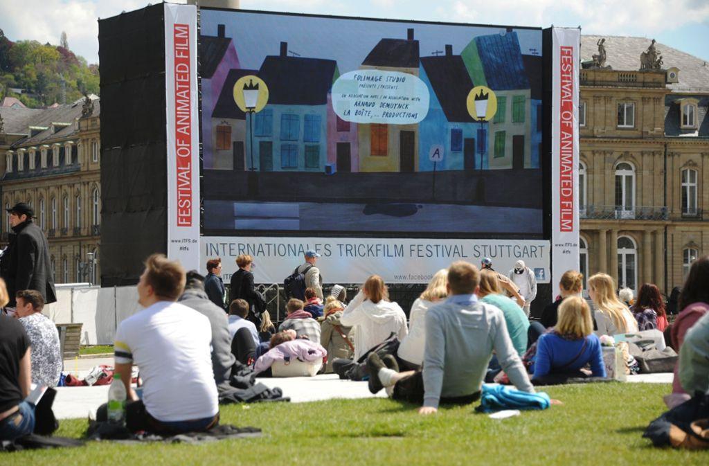 Bei schönem Wetter sitzen zahlreiche Menschen auf dem Schlossplatz vor der Leinwand des Trickfilmfestivals in Stuttgart. Foto: dpa