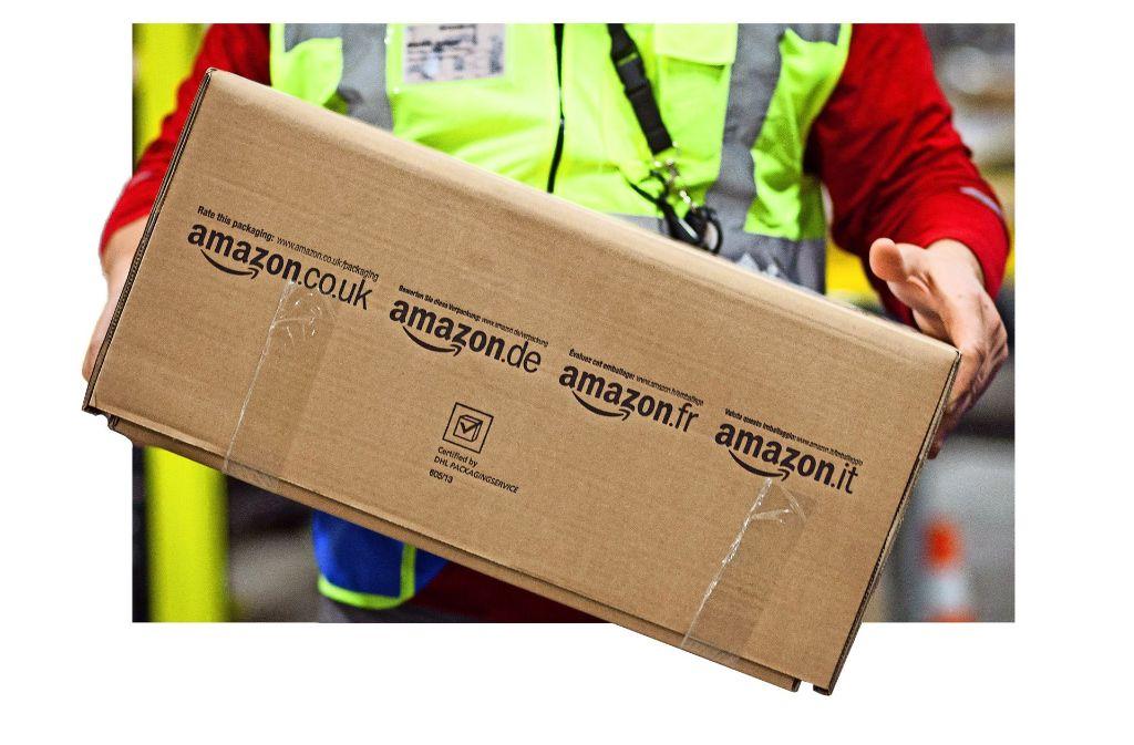 Ein Logistik-Arbeiter trägt bei Amazon in Pforzheim ein Paket. Foto: dpa