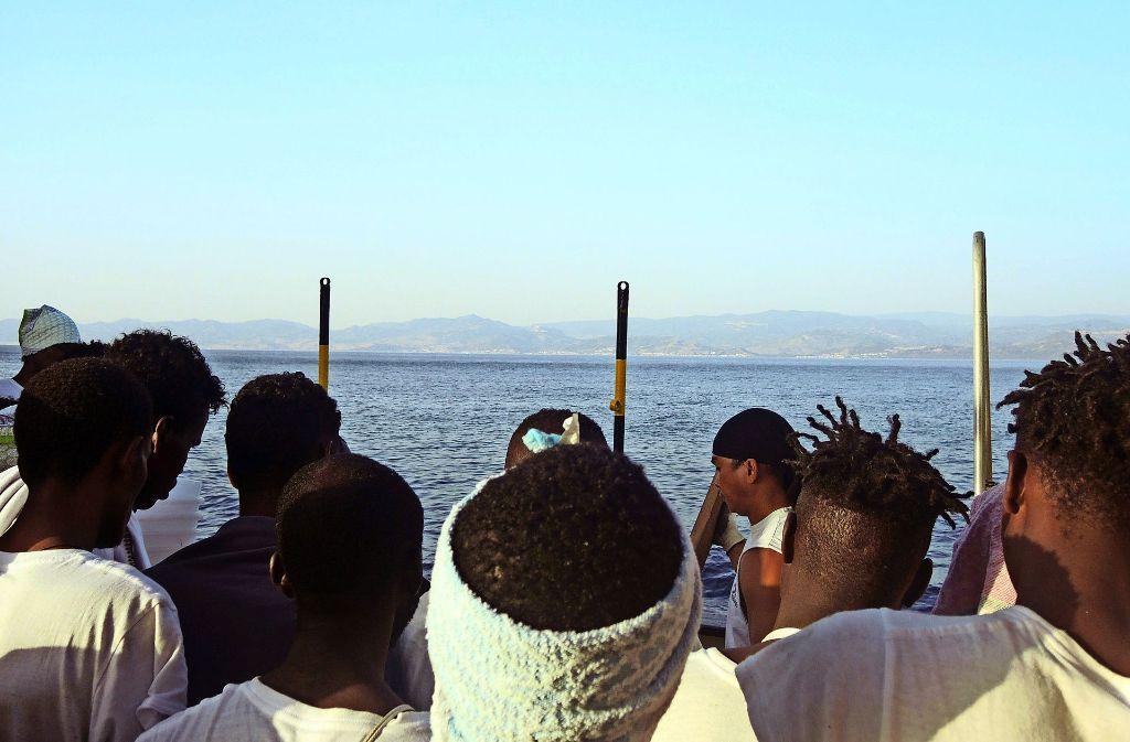 Migranten sitzen auf  einem Rettungsschiff vor der italienischen Küste. Foto: dpa