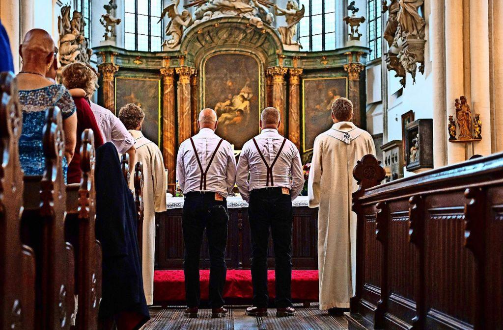 Trauung: Zwei Männer stehen mit zwei Pfarrern vor dem Altar. Foto: dpa