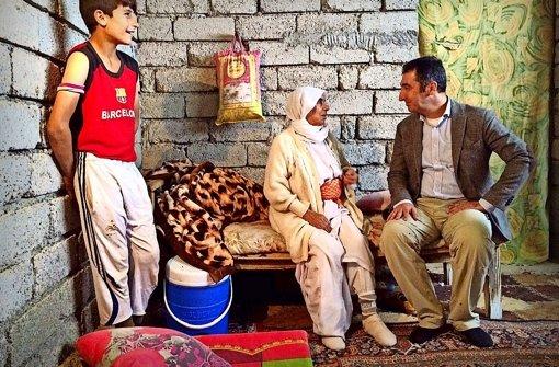 Cem Özdemir (rechts) sucht das Gespräch mit Flüchtlingen. Viele leben in Rohbauten. Foto: Knut Krohn