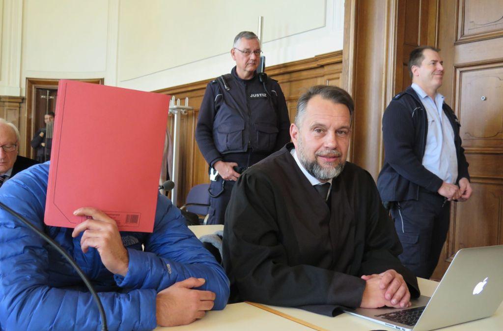 Einer der Angeklagten verdeckt sein Gesicht im Prozess. Foto: dpa/Miriam Steinruecken