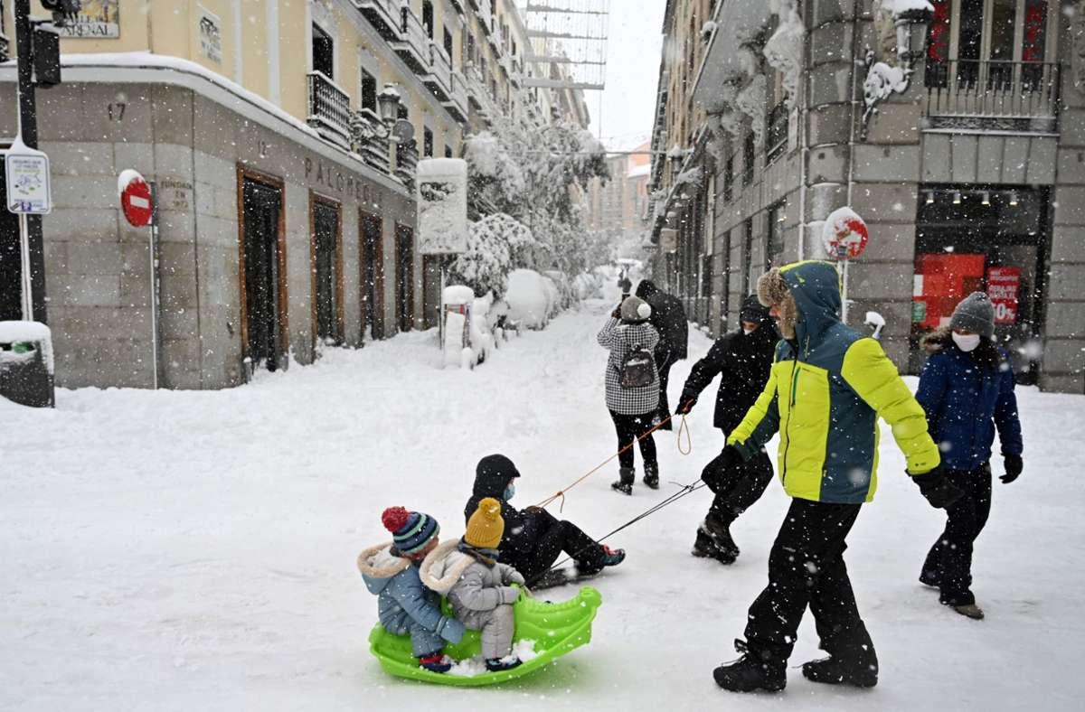 Neuschnee macht's möglich: Diese Kinder in Madrid erleben eine völlig neue Fortbewegungsart. Foto: AFP/Gabriel Bouys