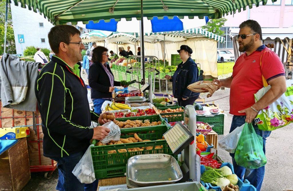 Walter und Sabine Schumacher (links) diskutieren an ihrem Obst- und Gemüsestand mit  Kunden über die Zukunft des Wochenmarkts am Ostendplatz. Vincenzo Paladino (rechts) würde am liebsten sofort eine Unterschriftenaktion für den Markt starten. Foto: Jürgen Brand