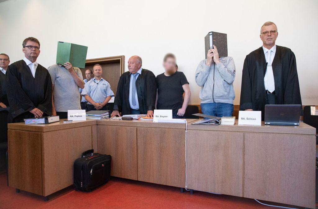 Die Angeklagten Heiko V. (von links nach rechts), Mario S. und Andreas V. stehen im Saal des Landgerichtes auf der Anklagebank neben ihren Verteidigern Jann Henrik Popkes (von links nach rechts), Jürgen Bogner und Johannes Salmen. Foto: dpa