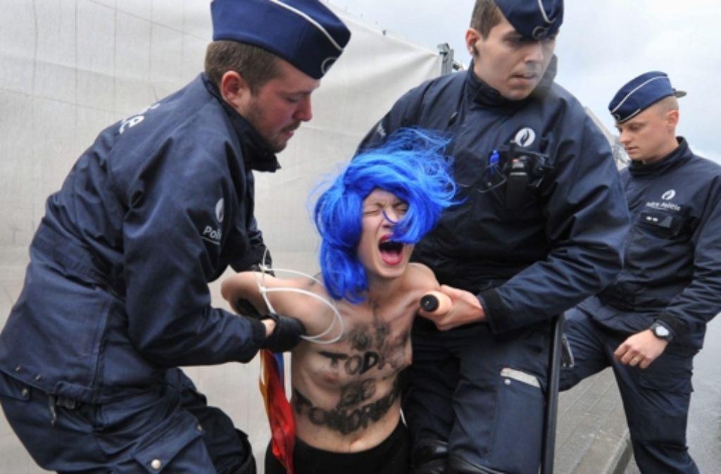 Polizisten führen am 4. Juni 2014 Femen-Frauen nach einer Protestaktion in Brüssel ab. Die Nackt-Aktivistinnen protestierten am Rande des G7-Gipfels. Foto: dpa