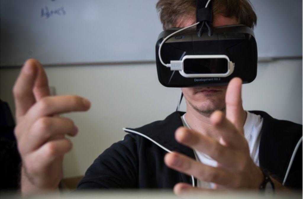 Andreas Schuller vom Fraunhofer-Institut IAO forscht mit der Virtual-Reality-Brille Oculus. Ein zusätzlicher Sensor registriert die Position seiner Hände und blendet sie in das Bild der Brille ein: So kann man im seinen Fingern beispielsweise im virtuellen Bild auf Knöpfe drücken. Foto: Achim Zweygarth