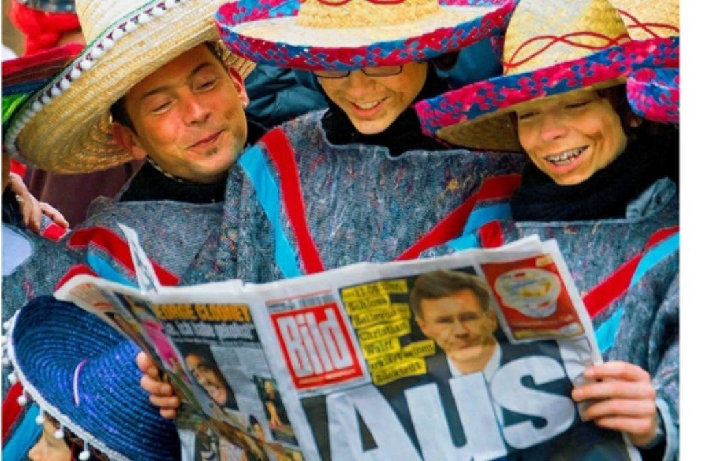 """Narren lesen am 18. Februar 2012 die """"Bild""""-Zeitung. Foto: dpa"""