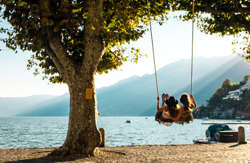 Zwei junge Frauen sitzen auf der Swing und schaukeln über den Lago Maggiore in den Sonnenuntergang.
