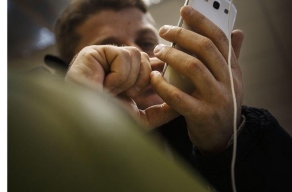 Das Smartphone ist die Nabelschnur, die Salim Aziz in Leonberg mit der fernen Heimat verbindet. Foto: Gottfried Stoppel