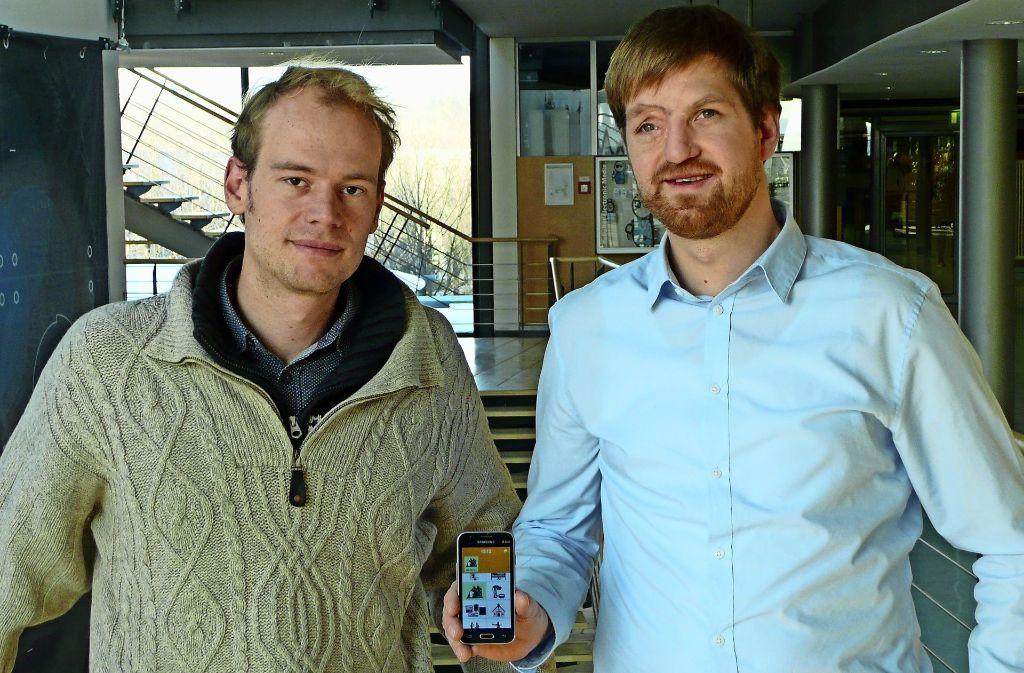 Thomas Daum (links) und Hannes Buchwald mit der Smartphone-App, die den Bauern in Sambia bei der Zeiterfassung hilft. Foto: Christoph Kutzer