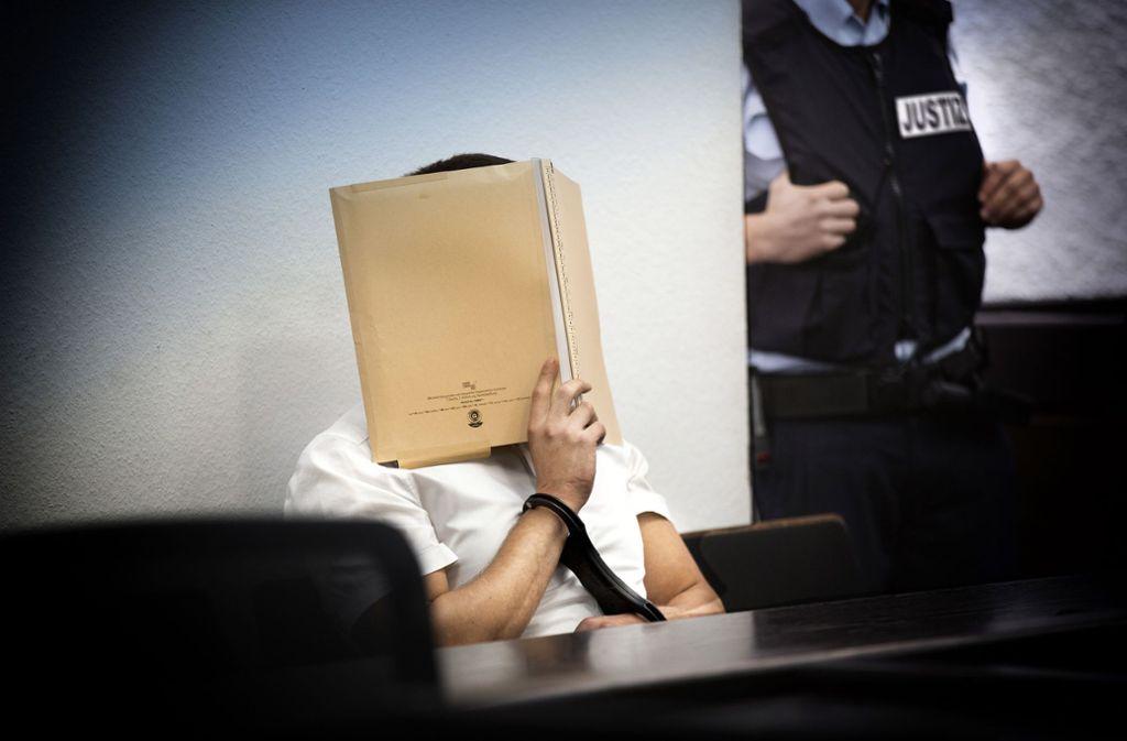 Der 31-jährige Angeklagte verdeckt kurz vor der Urteilsverkündung sein Gesicht mit einem Aktenordner. Foto: