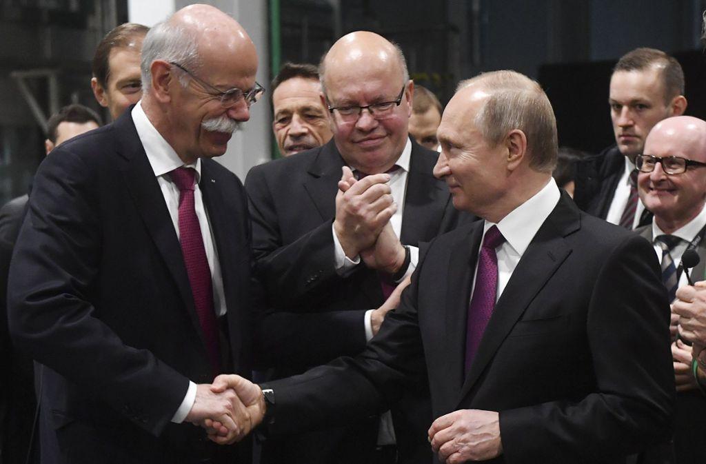 Vorsichtige Annäherung allen politischen Differenzen zum Trotz: Daimler-Chef Dieter Zetsche (li.) begrüßt Russlands Präsident Putin (re.). Bundeswirtschaftsminister Peter Altmaier (CDU) applaudiert. Foto: Sputnik