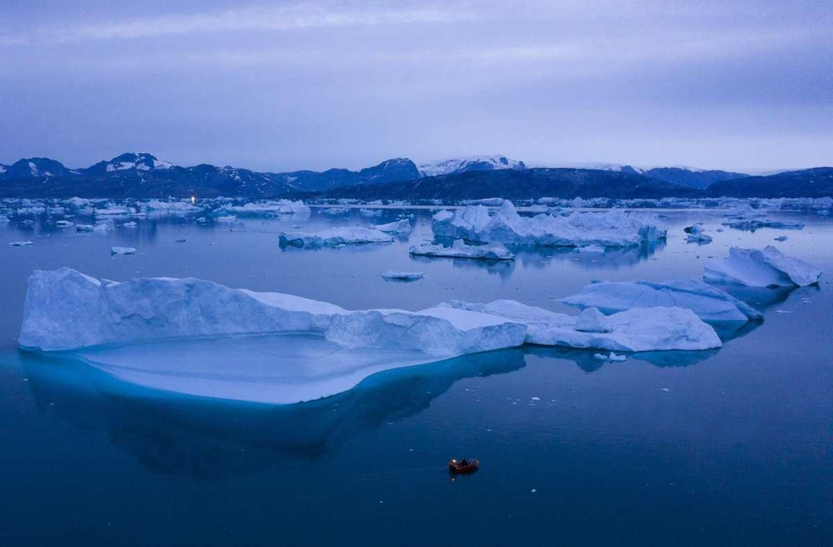 Ein kleines Boot schwimmt inmitten eines Eisbergfeldes bei Kulusuk. Grönland ist besonders vom Klimawandel betroffen. Foto: /Felipe Dana/dpa