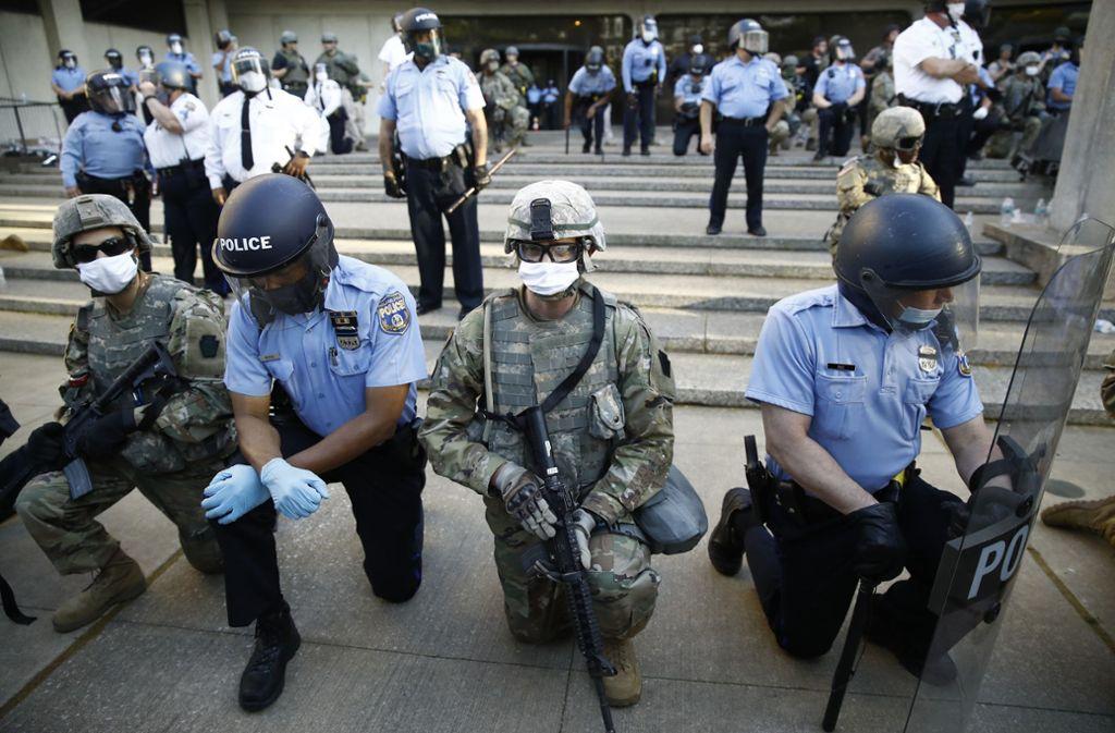 Mitarbeiter der Polizei von Philadelphia und der Nationalgarde von Pennsylvania knien während eines Protestmarsches nieder. Foto: dpa/Matt Rourke